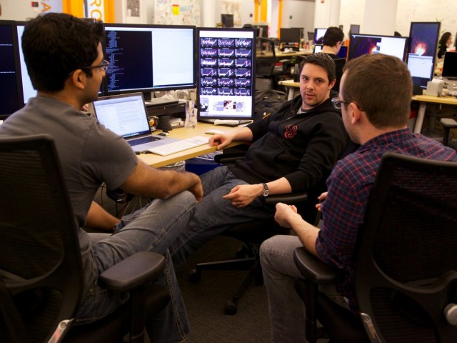 back-in-the-main-work-area-ad-server-engineer-mike-wright-center-is-meeting-with-product-manager-mike-mcneeley-right-and-ad-server-engineer-shareyas-prasad-left